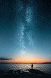 canvas print picture - Silhouette of a man looking up on stars of the milky way with last light of sunset glows on the horizon