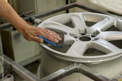 Fotografía  Master body repair man is working on preparing the surface of the aluminum wheel