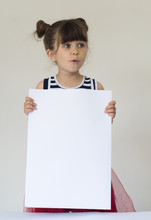 Portrait Of Surprised Girl Holding A Blank Sign White Paper.