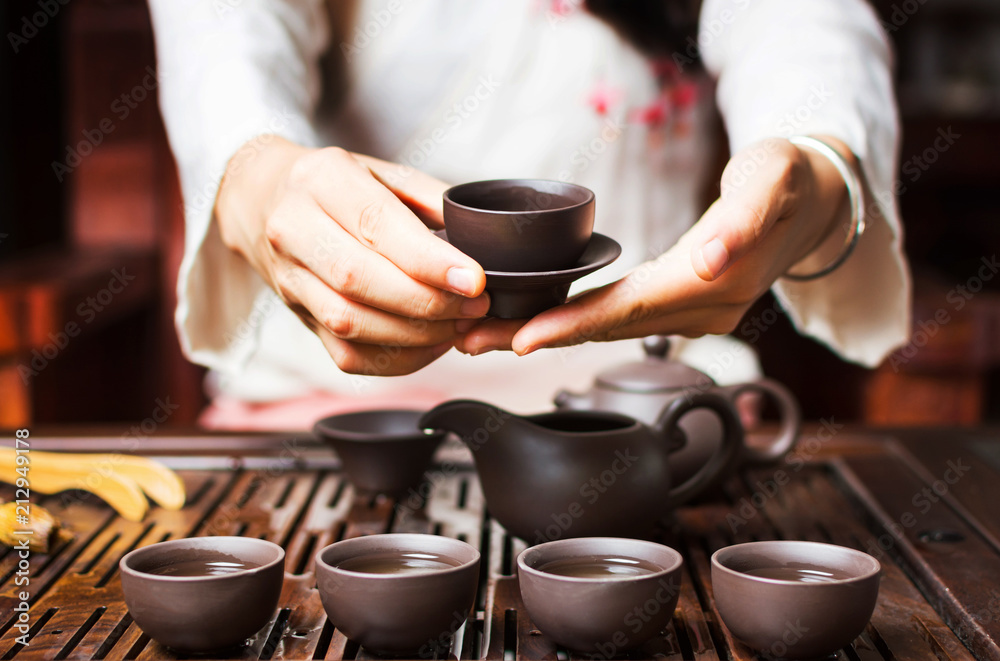 Fototapeta Woman serving Chinese tea in a tea ceremony