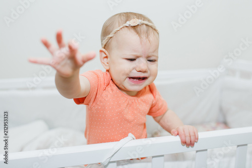 Portrait of cute baby girl crying in crib at home — Photo by Iatanni Fotobehang