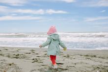 Portrait Of Cute Toddler Girl Walking On Sandy Beach In Spring.