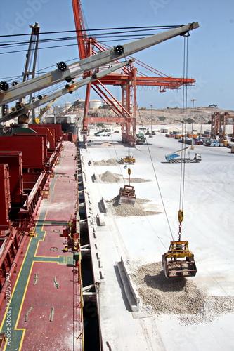 Staande foto Poort Грузовой терминал ,погрузка гипса судовыми кранами на балкер, порт Салалах, Оман, Индийский океан.