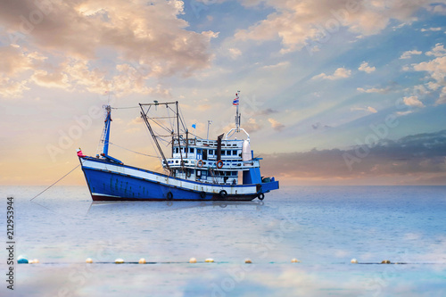 Blue - White Fishing Boat In The Sea And Dramatic Clouds At Sunrise.