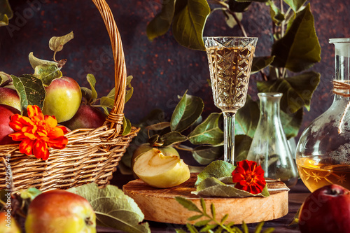 Tableau sur Toile Apple cider in a glass and a decanter and basket with ripe apples on a wooden ta
