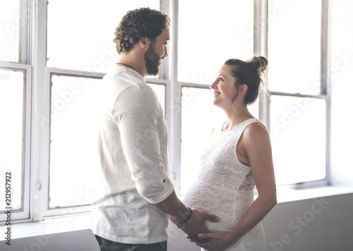 Photo  Handsome man and his beautiful pregnant wife standing near the window at home
