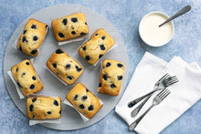 Individual Blueberry Loaf Cakes With Cake Forks And A Bowl Of Cream.