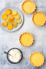 Lemon Tarts With A Plate Of Candied Lemon, Lime And Orange Slices And A Bowl Of Yoghurt.