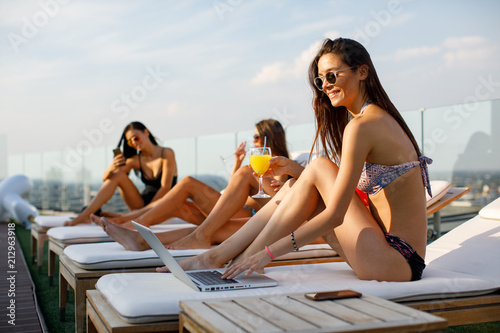 Photographie Four attractive women enjoy sunbeds in penthouse