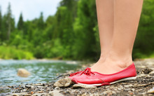 Female Legs In Red Shoes On A Background Of Landscape