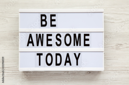 'Be awesome today' word on lightbox over white wooden background, from above плакат