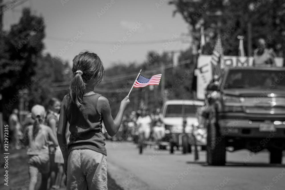 Fototapeta Girl waving American flag at parade in black and white