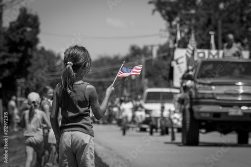 Obraz na plátně Girl waving American flag at parade in black and white