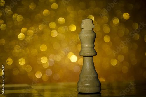 Fotografía  Pieza de ajedrez en fondo dorado brillante. Rey de madera.