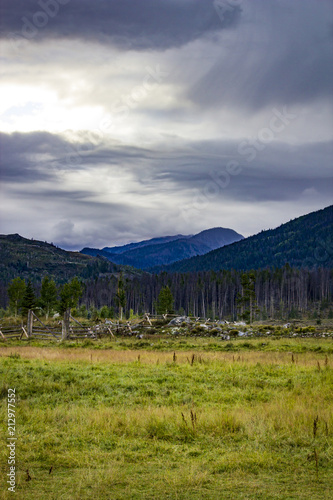 Fényképezés  Peaks of the Rocky Mountains Jut out into a Stormy Sky with a Meadow in the Fore
