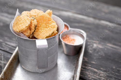 Fototapeta Close up on deep fried pickle slices in an old metal container obraz