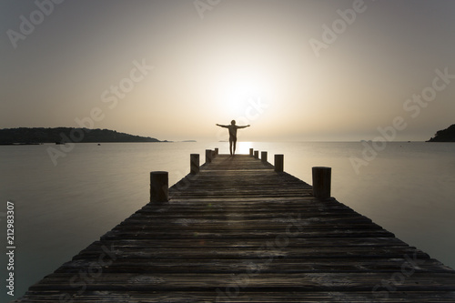 Fotomural  Person steht mit offenen Armen bei Sonnenaufgang am Steg