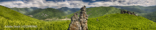 Fond de hotte en verre imprimé Colline Panoramic landscape: a large rocky peak against the background of green mountains, hills and smaller rocks, a contrasting blue sky and clouds. HDR image with polarisation lens filter