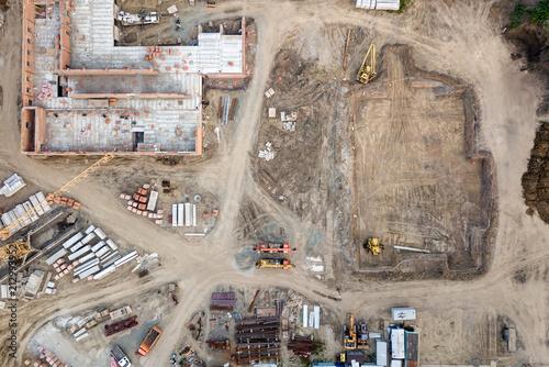 widok-z-lotu-ptaka-budowa-wielopietrowych-domow-mieszkalnych-za-pomoca-dzwigu-budowlanego-koparki-ladujacej-wywrotke-w-nowej-dzielnicy-mieszkalnej-miasta