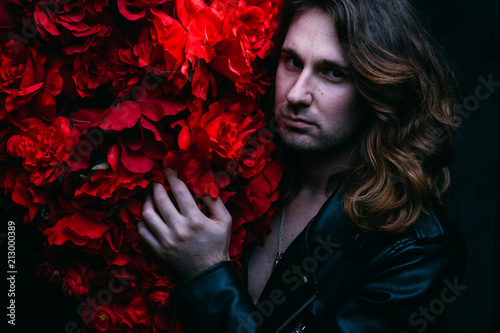 Fotografía brutal man in a leather jacket on a naked body with long hair stands near the decor with red flowers flowers