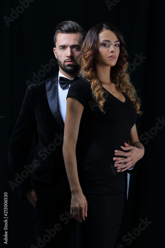 embraced elegant couple holding hands and look at the camera