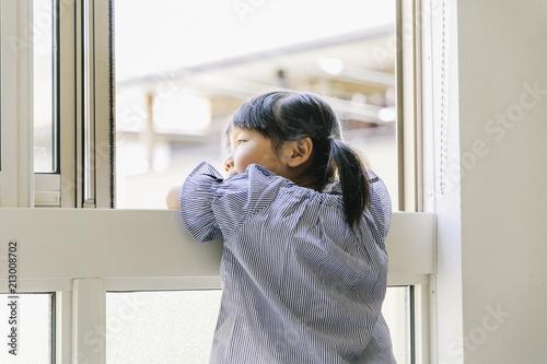 窓から外の様子を見ている女の子