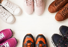 Three Pairs Of Colorful Running Trainers / Exercise Shoes On The Floor Of A Sport / Shoe Shop. Potential Copy Space On Floor.