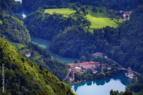 Fototapeta Beautiful alpine town in the river valley with emerald water and green meadows. obraz
