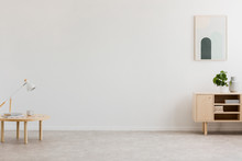 Desk Lamp On A Small Table And A Simple, Wooden Cabinet In An Empty Living Room Interior With White Wall And Place For A Sofa. Real Photo.