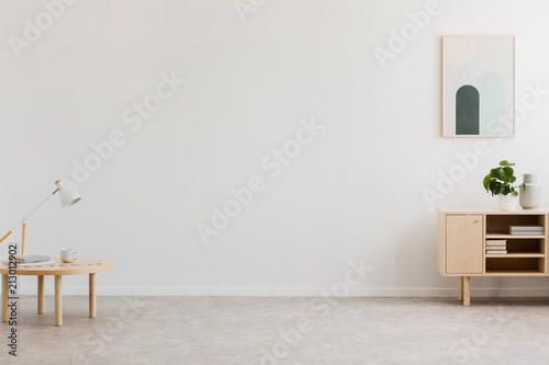 Obraz Desk lamp on a small table and a simple, wooden cabinet in an empty living room interior with white wall and place for a sofa. Real photo. - fototapety do salonu