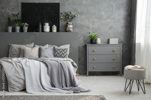 Cuadros en Lienzo Monochromatic grey bedroom interior with a big bed with throws and pillows and a drawer cabinet against a wall with a black canvas