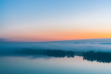 Broad Mystical River Flows Along Diagonal Shore With Silhouette Of Trees And Thick Fog. Orange And Pink Glow In Predawn Vanila Sky. Morning Atmospheric Landscape Of Majestic Nature In Tender Tones.