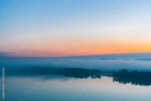 Broad mystical river flows along diagonal shore with silhouette of trees and thick fog Poster