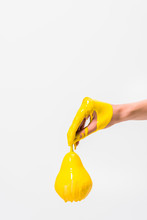 Cropped Image Of Woman In Yellow Paint Holding Pear In Hand Isolated On White