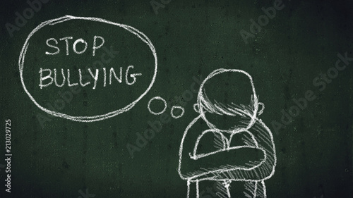 sad young boy sitting on the floor with text stop bullying written with chalk on chalkboard Poster Mural XXL