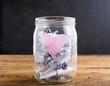 canvas print picture - Einmachglas mit rosa Herz und zusammengerollten Notizzetteln auf einem Holztisch, schwarzer Hintergrund, Textfreiraum