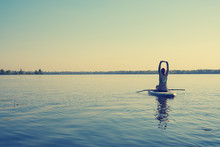 Female Practicing Yoga On A SUP Board During Sunny Morning