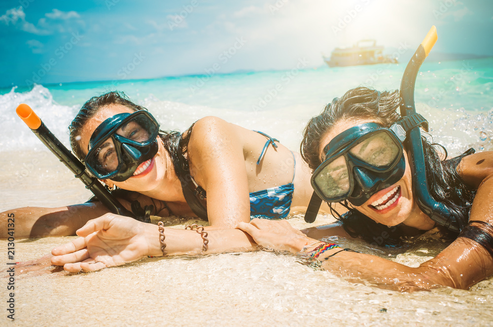 Fototapeta Two happy girlfriends with snorkeling mask enjoying on the beach