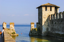 The Walled And Fortified Inner Harbour And Watch Tower In The Walled Town Of Sirmione, Lombardy, Italy