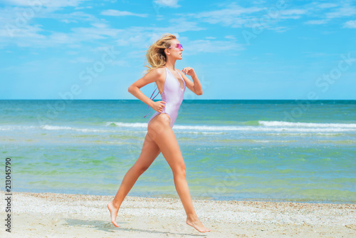 Fototapeta A beautiful young girl with blond hair and an excellent figure in a swimsuit runs along the beach on a sunny summer day obraz na płótnie