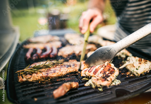 Fotografia, Obraz Unrecognizable man cooking seafood on a barbecue grill in the backyard
