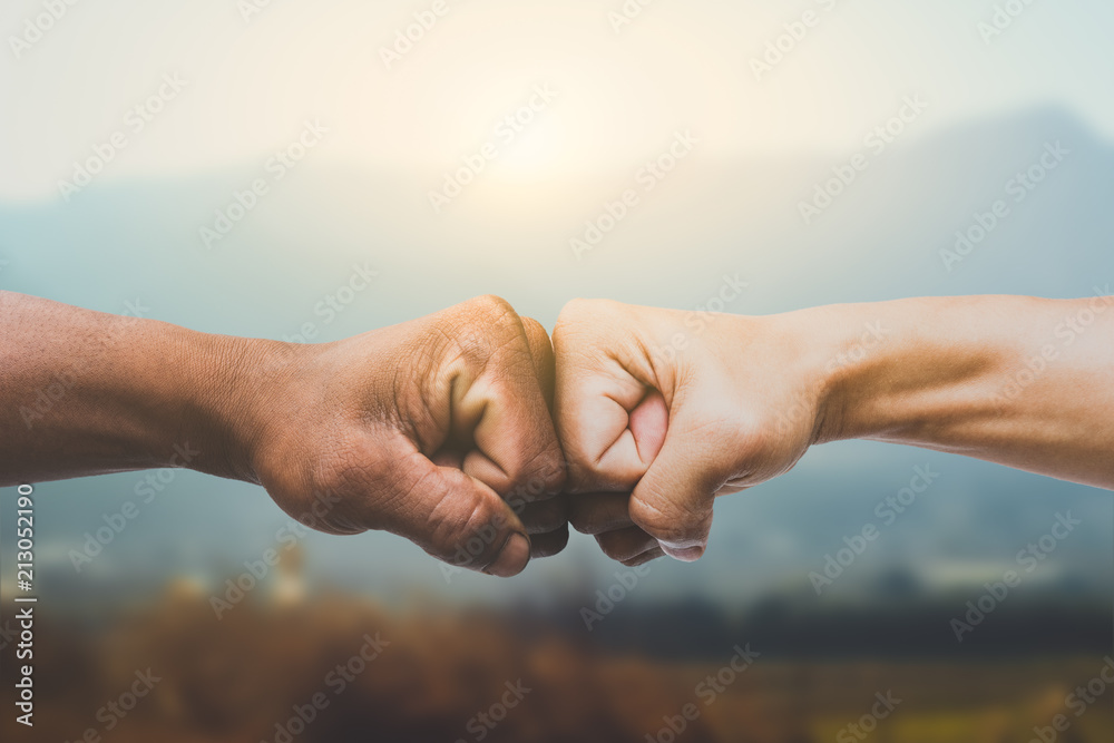 Fototapeta Man giving fist bump in sun rising nature background. power of teamwork concept. vintage tone