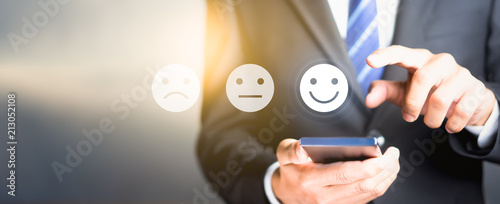 Businessman pressing happy icon, Customer service evaluation concept..
