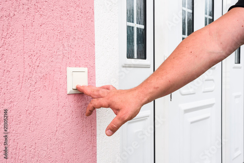 Obraz na plátně  hand ringing on doorbell on pvc front door