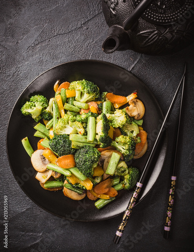 Photo  Top view of hot stir fried vegetables on black plate
