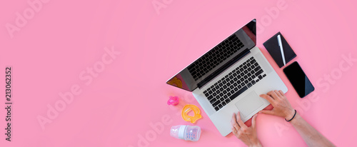 Working mom top view flatlay of workplace baby items and laptop with phone - 213062352
