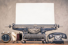 Retro Aged Black Typewriter With Large Paper Blank, Classic Telephone, Old Alarm Clock And Mail Envelopes Holder On Wooden Table Front Concrete Wall Background. Vintage Style Filtered Photo Photo