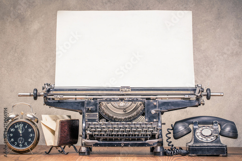 Papiers peints Retro Retro aged black typewriter with large paper blank, classic telephone, old alarm clock and mail envelopes holder on wooden table front concrete wall background. Vintage style filtered photo photo