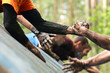 Folks help each over during mud race with obstacle course.