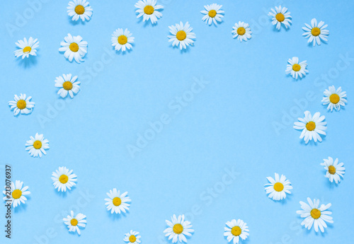 Tuinposter Bloemen Chamomile flowers frame on the blue background. Top view. Copy space